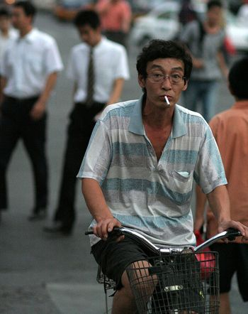 Chinese man riding bike and smoking