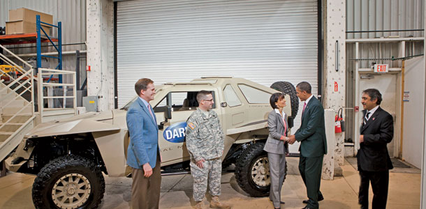 Jay Rogers, CEO of Local Motors (left), and DARPA's Nathan Wiedenman look on as Dugan shakes President Barack Obama's hand. The XC2V (behind), a combat test vehicle designed through crowdsourcing, was unveiled at Carnegie Mellon University, in June. | Photo by Douglas Sonders