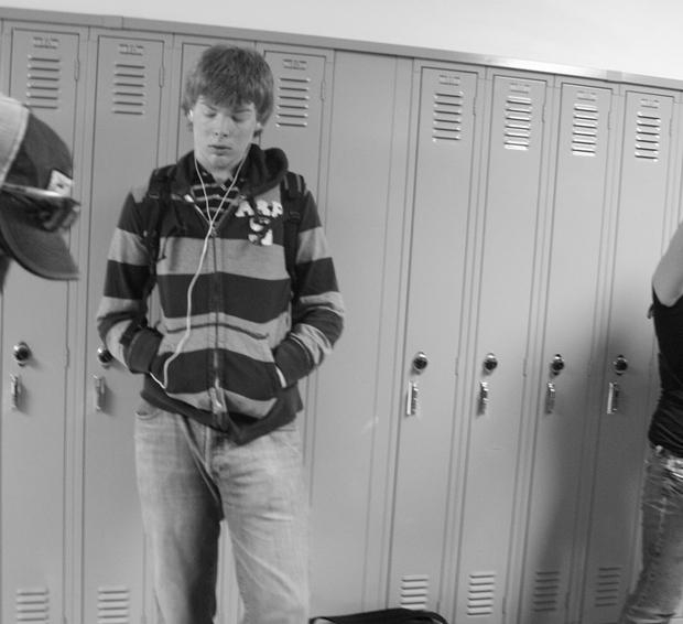 Kid listening to music in front of locker