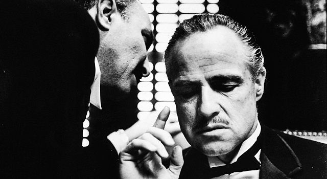 Black and white picture of Godfather Vito Corleone (Marlon Brando) seated with consigliere Tom Hagen (Robert Duvall) whispering in his ear. Both wearing tuxedoes, Corleone raises his index finger.