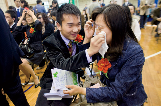 Second High student Aidan Liu, above, wipes away his mother Hung Wang's tears at the coming of Age ceremony held each May for the seniors. The students write letters to thank their parents and receive copies of the chinese constitution, middle.
