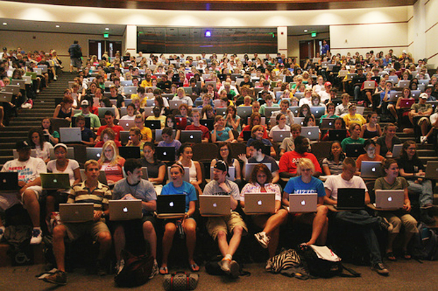 journalism students in lecture hall using mac laptops